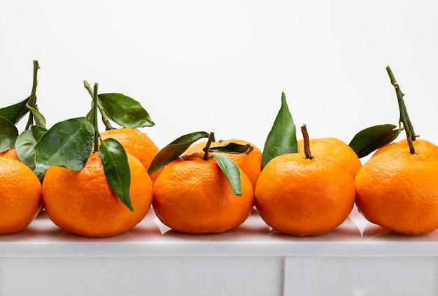 Свежие и сырые мандарины с зелеными листьями на белом столе