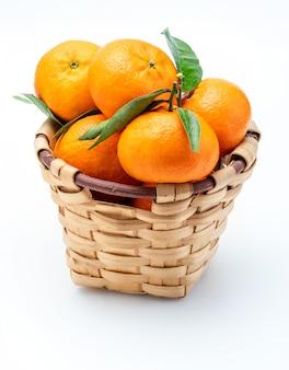 Свежие и сырые мандарины с зелеными листьями в деревенской плетеной корзине.
