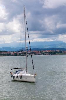 Спортивный парусник пришвартовался в бухте со спокойным морем и угрожающим небом