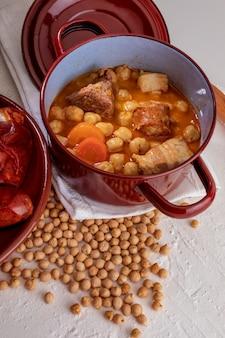 ヒヨコマメ、肉、野菜の自家製ヒヨコマメのシチューマドリッドシチュー(チョリソ、ブラッドソーセージ、ハム、ニンニク、タマネギ、ニンジン、仔牛、鶏)。典型的なスペイン料理