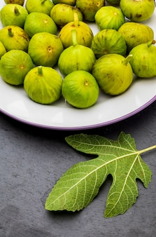 新鮮で熟した緑のイチジク。イチジクの葉。