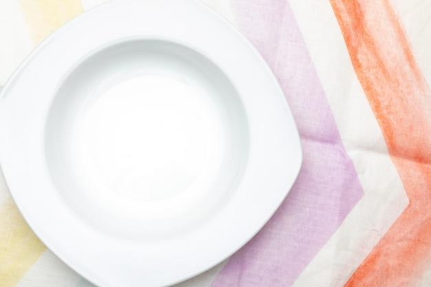 空の白いプレート。パステルカラーの繊細なテーブルクロス。食べ物とテキストを含めるためのコンセプト。