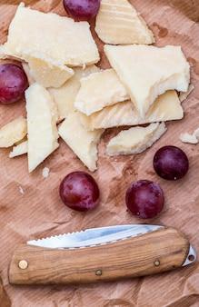 赤ぶどうと羊の塩漬けチーズ(マンチェゴタイプ)。茶色の紙の上に素朴な外観。