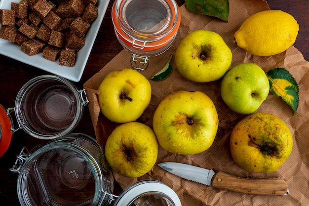 Ингредиенты для приготовления варенья и яблочного пюре (желтый, реинетас). с сахаром, лимоном и стеклянными банками.