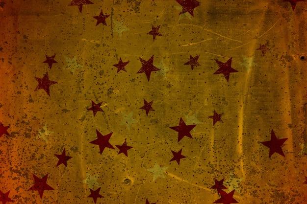古い金属の質感と星(赤と黄色)。金、赤、銀、オレンジ色。