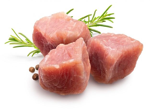Сырые и свежие (нарезанные кубиками) кусочки мяса индейки (курица). с веточкой розмарина и перца (специи).