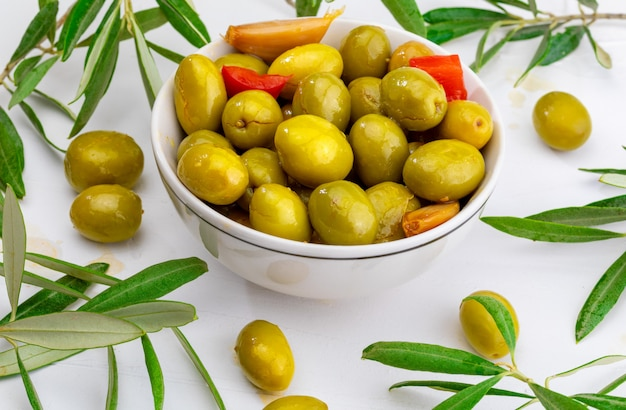 赤唐辛子とニンニクを含む職人オリーブ(エキストラバージンオリーブオイル、酢、スパイスの缶詰)。前菜のコンセプト。