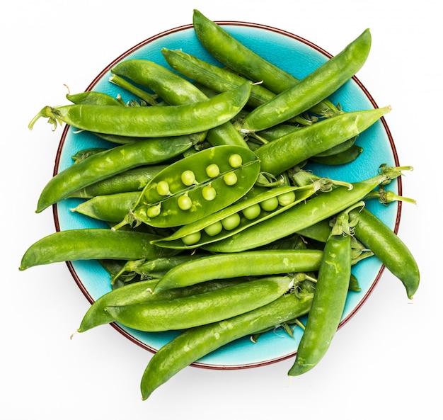 グリーン、柔らかく、新鮮で生のエンドウ豆。青い色の正確なボウル。孤立した