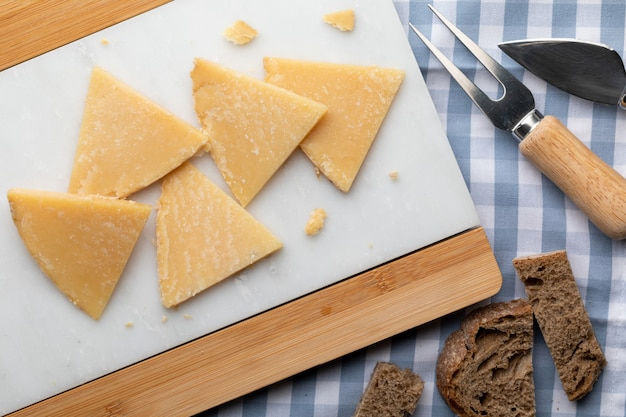 硬化羊のチーズ。白い大理石とパンで細かく切る。チーズ用のフォークとナイフ。上面図。