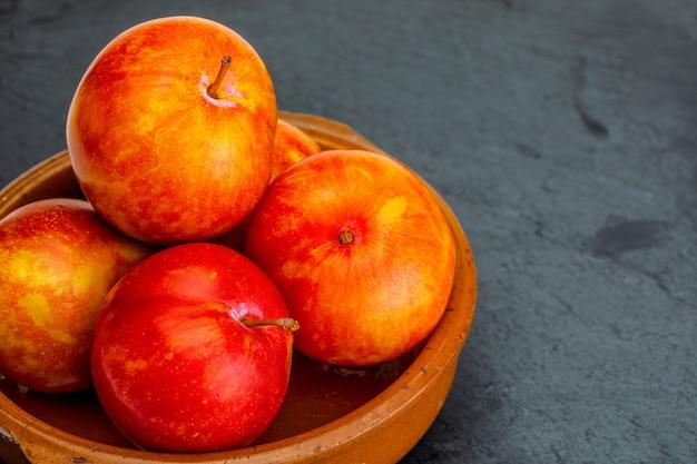 Куча апельсиновых слив в миске