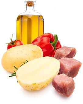 Кубики мяса рядом с картофелем и красным перцем