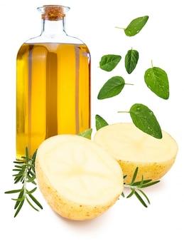 Картофель возле бутылки оливкового масла и орегано