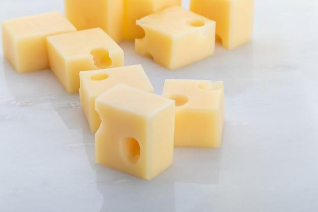 Порции (кубики, кубики) швейцарского сыра эмменталь с скребком. текстура отверстий и альвеол. на белом мраморном фоне.