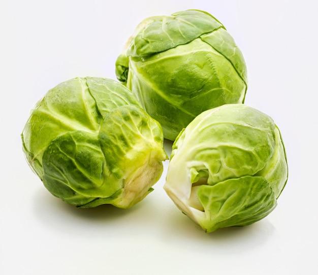Крупный план сырой, свежей и целой брюссельской капусты (капуста - капуста белокочанная). изолированные на белом фоне