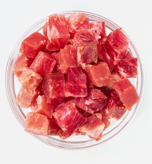 Иберийскую ветчину (серрано) нарезать кубиками (нарезать кубиками). в стеклянной посуде. изолированные на белом