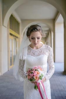 アーチ型のギャラリーで花束を持って立っている花嫁