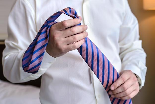 紫のネクタイのクローズアップを保持している男性の手