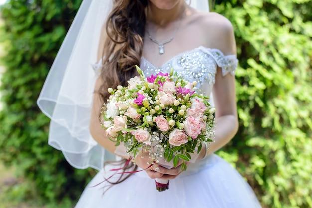 花嫁はウェディングブーケを持っています