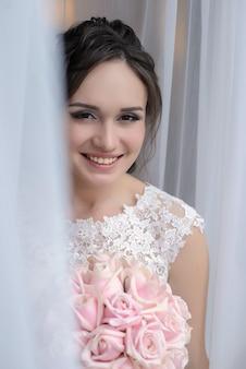 Красивая невеста стоит у окна с букетом розовых роз и улыбок