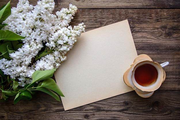 Белая махровая персидская сирень, чашка чая и лист бумаги на деревянном фоне