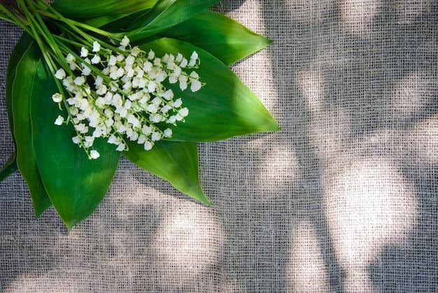Весенний букет из белых ландышей на фоне мешковины