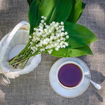Весенний букет из ландышей в белой корзине и чашке чая