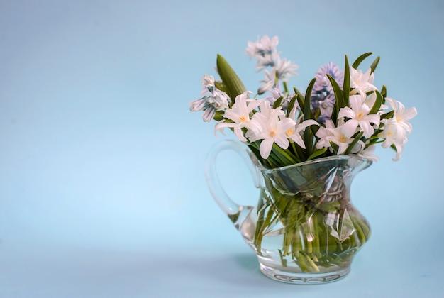 Букет из белых цветов в стеклянной вазе на синем фоне