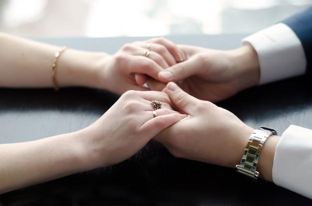 テーブルの上の手を繋いでいる恋人
