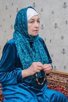 年配のイスラム教徒の女性が祈りを読む