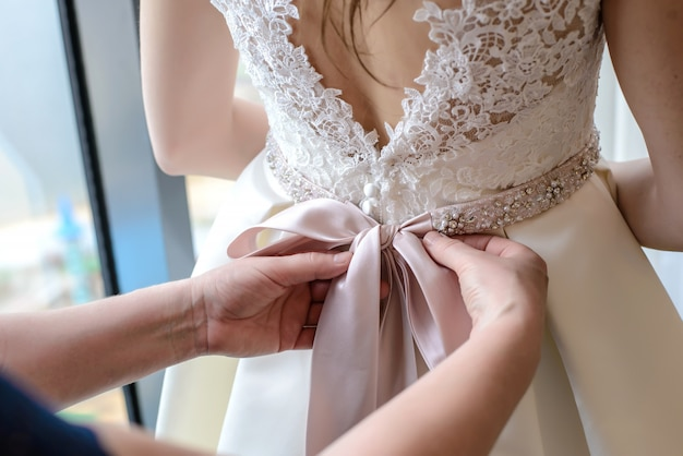 女性の手は花嫁のドレスに弓を結ぶ