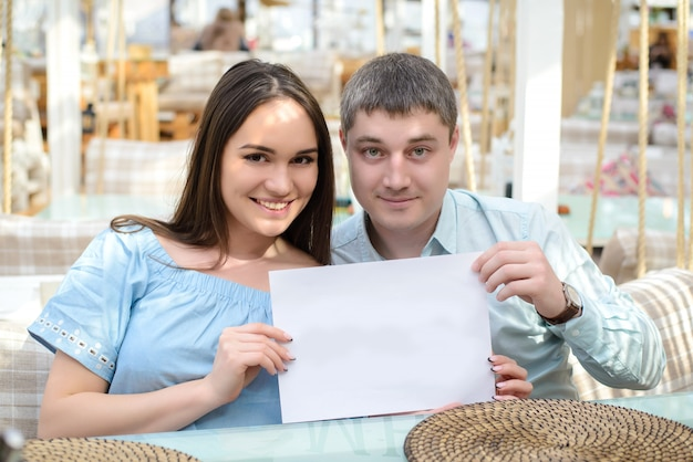 Парень и девушка держат чистый лист бумаги