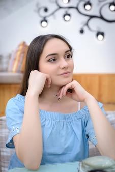 テーブルに座って美しい少女