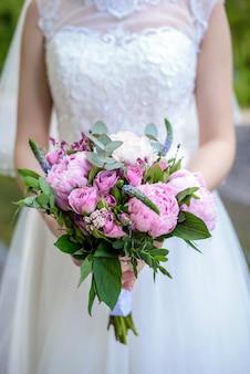 花嫁は牡丹のクローズアップのウェディングブーケを保持しています