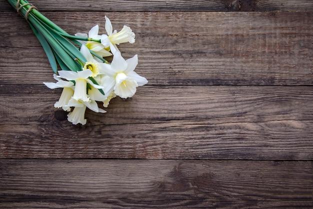 木製のテーブルに黄色い水仙と白の花束