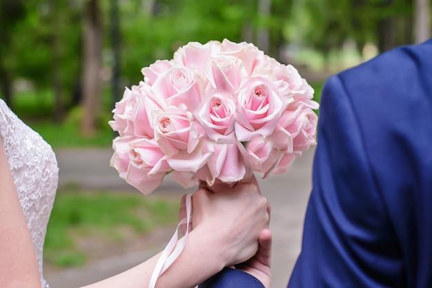 新郎新婦のクローズアップの手にピンクのバラのウェディングブーケ