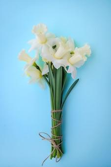 青の背景に白の水仙と明るい黄色の花束