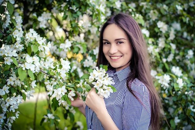開花のリンゴの木の横にある若い女の子