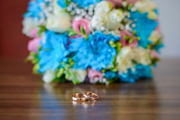 Обручальные кольца и свадебный букет на деревянном столе