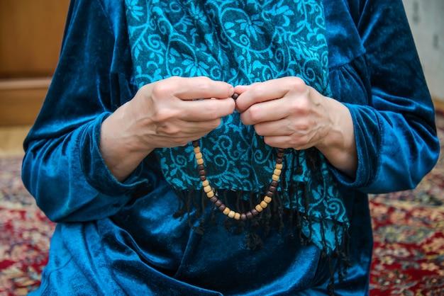 高齢者の女性の手の中のイスラム教徒のロザリオ