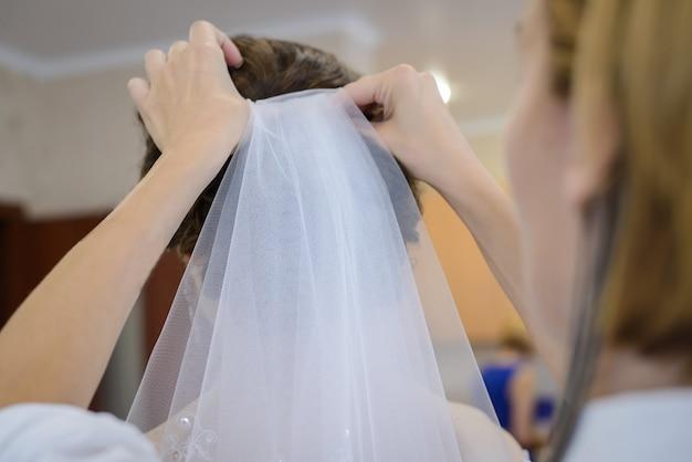 Парикмахер прикрепляет вуаль к свадебной прическе невесты