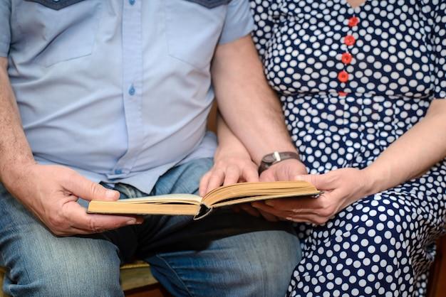 Пожилая пара читает книгу вместе крупным планом