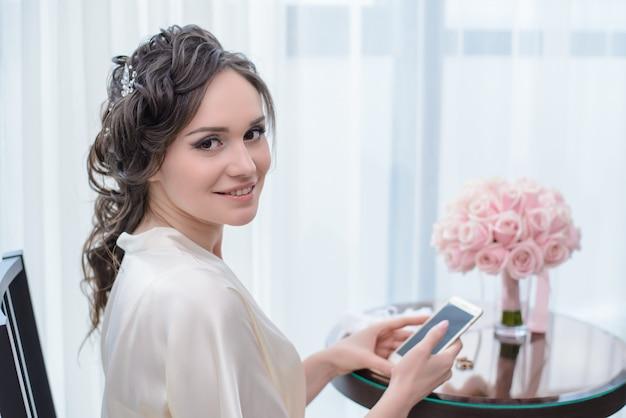 電話で窓際に座っている朝の花嫁
