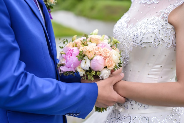 Свадебный букет в руках жениха и невесты