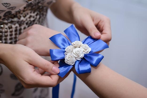 花嫁の友人は手にリボンを結びます