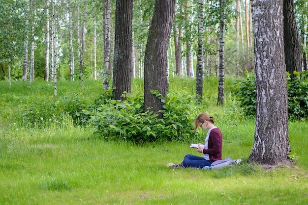 公園の芝生の上の本を読んでいる女の子