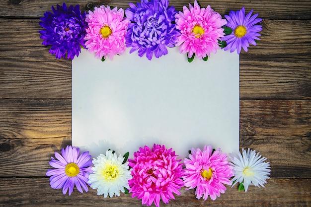 Рамка из цветов астр на деревянном фоне