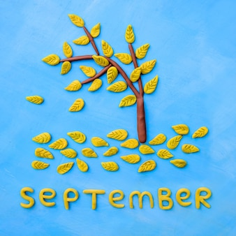 Пластилиновое желтое осеннее дерево и слово сентябрь