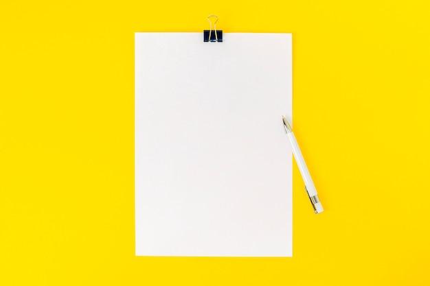 白い事務用紙の空のシートは、黄色の背景の中央に文房具クリップとペンで固定されています。モックアップ、ボードの発表、情報、ステートメント、学校の場合は空白。フラット横たわっていた。