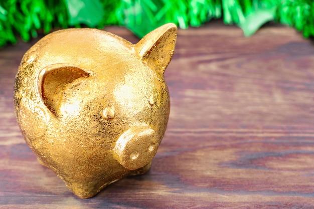 黄金の豚年記号はクリスマスツリーの枝を持つ木製のテーブルの上に立つ