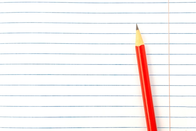 Красный карандаш на фоне книги крупным планом, макет, копией пространства